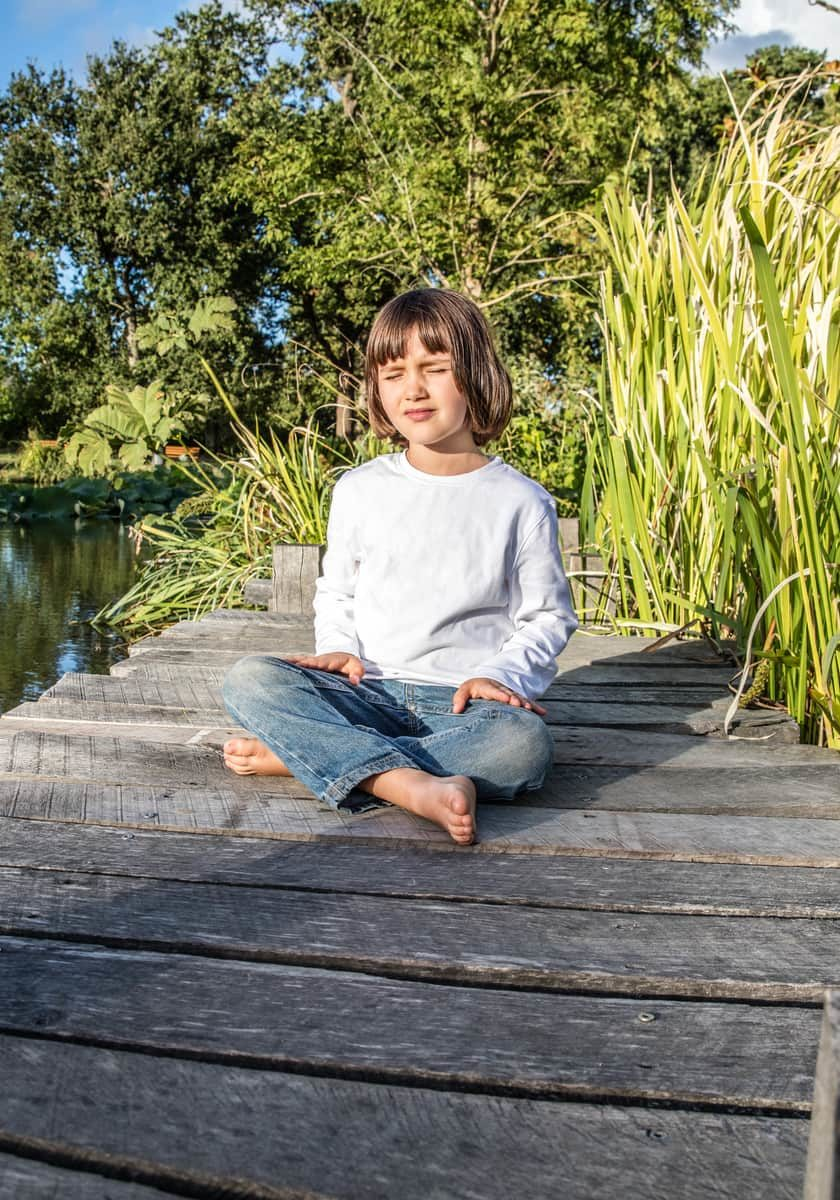 relaxed beautiful young 5-year old child cross-legged with bare feet breathing alone, closing eyes for yoga and meditation near water and trees