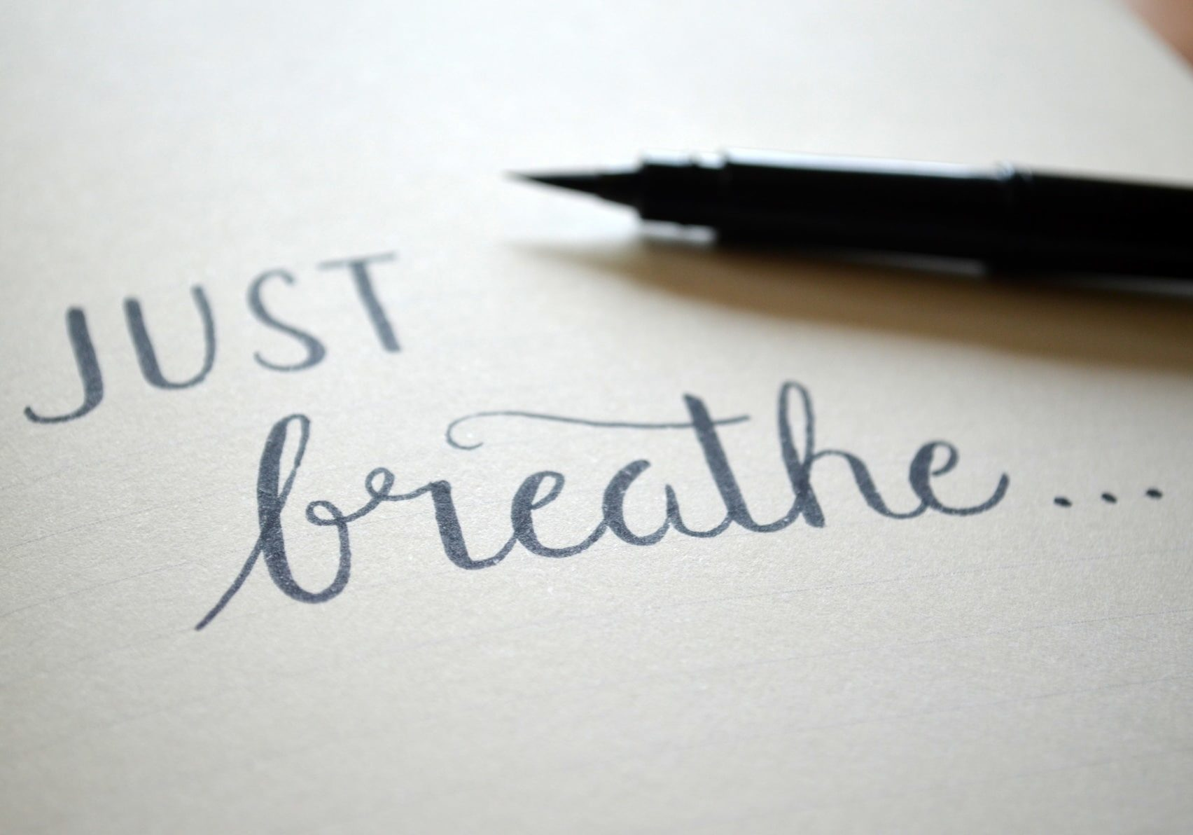 JUST BREATHE handwritten on notepad